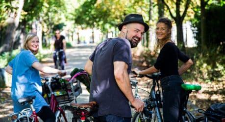Menschen lachen in die Kamera und stehen an ihren Fahrrädern