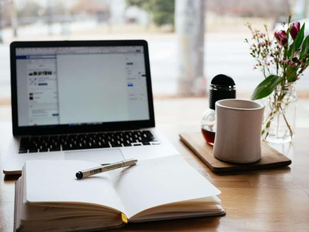 arbeiten-am-laptop-mit-schreibblock-und-kaffee