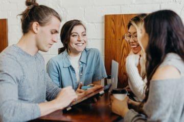 Junge Menschen sitzen an einem Tisch und besprechen sich und lachen.