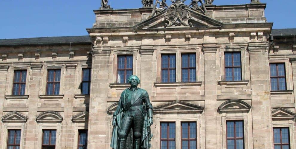 Altes festliches Gebäude mit einer Statur eines Mannes davor